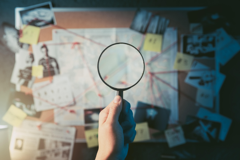 A magnifying glass observes criminal evidence