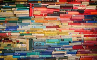 Stacks of colourful books, by Robert Anasch