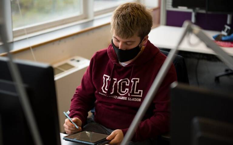 Male student at desk, wearing a mask
