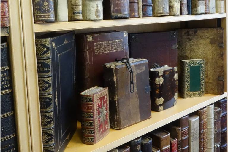 A display of rare and historical books on a shelf, including Christian and Jewish texts with gold leaf on their covers, a book with a tortoiseshell cover, and a book attached to a chain.