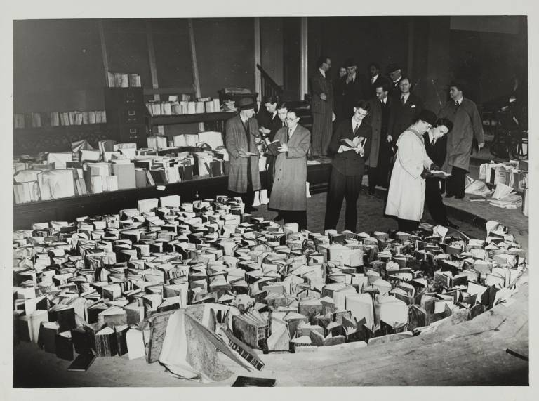 A photograph from 1941; men stand in the main library, inspecting a large number of books that stand with their pages open, drying out after being soaked in water to prevent further fire damage after the bombing of UCL's main building.