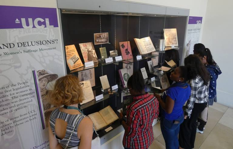 A group of young women looking at an exhibition held in UCL Main Library. The exhibition is titled 'Dangers and Delusions' and is about the women's suffrage movement. Books, photographs and magazines are on display.