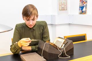 Student examining a rare book from UCL Special Collections