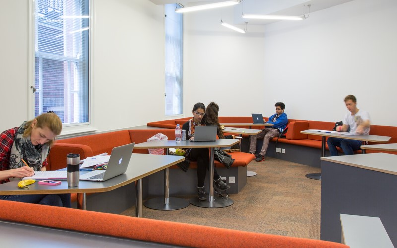 Library users sitting at desks, studying, inside the UCL Cruciform Hub