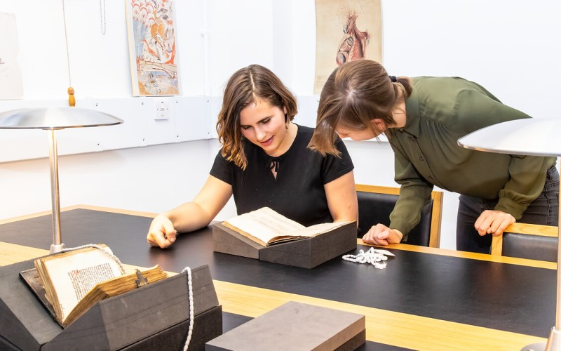 Two users looking at a rare book from UCL's Special Collections