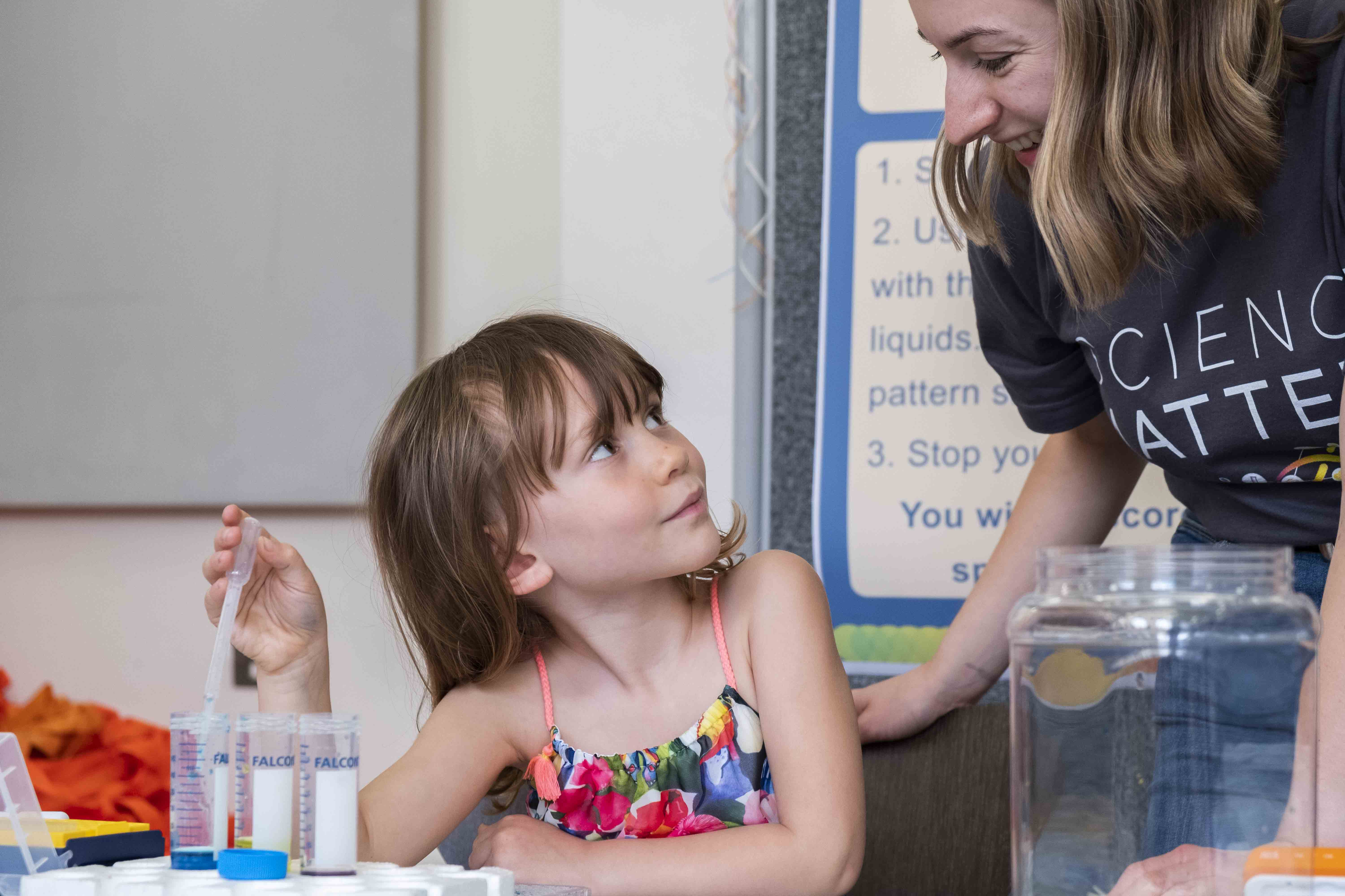 Scientist engaging with young girl at science fair