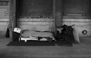 black and white photo of a homeless person sleeping on street