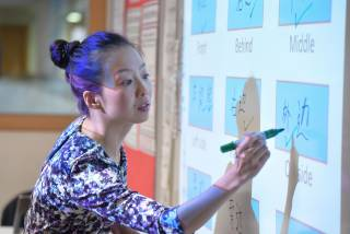 teacher writing Mandarin on a whiteboard