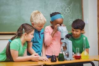 group of children looking through a microscope
