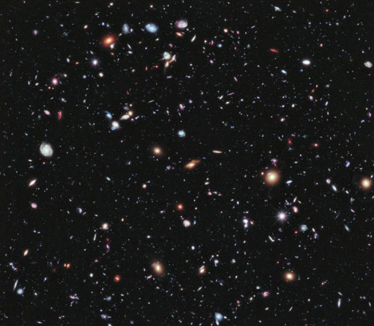 In this image — one of the deepest ever taken by the Hubble Space Telescope — most of the luminous sources are distant galaxies. The expansion of the Universe causes a cosmological redshift, so that the most distant sources appear reddest. The work …