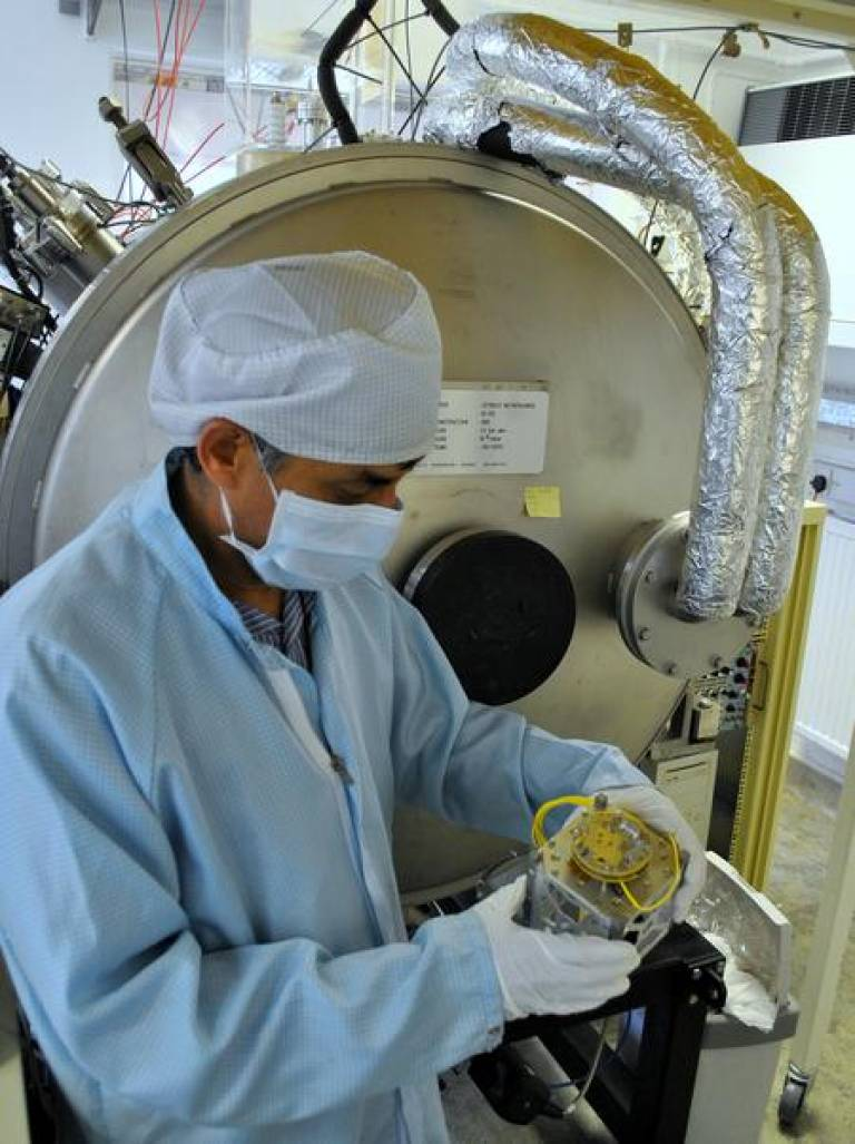 Dhiren Kataria (MSSL) holds a CubeSat chassis in front of a vacuum chamber