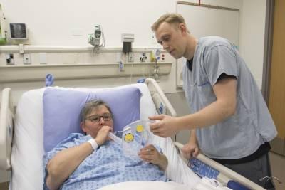 Male nurse treats female patient in hospital bed