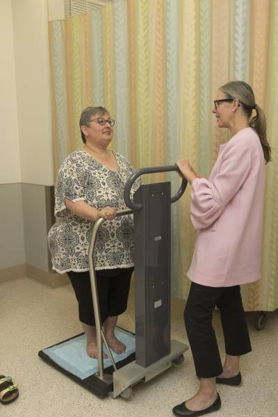 Woman being weighed by a doctor