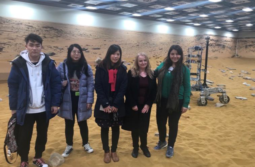 students of the department stand on a martian landscape testing facility