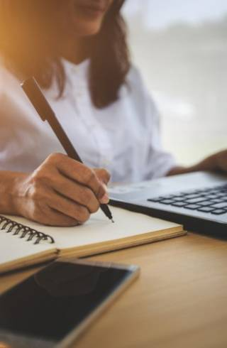 Photo of woman looking at laptop whilst writing on a notebook