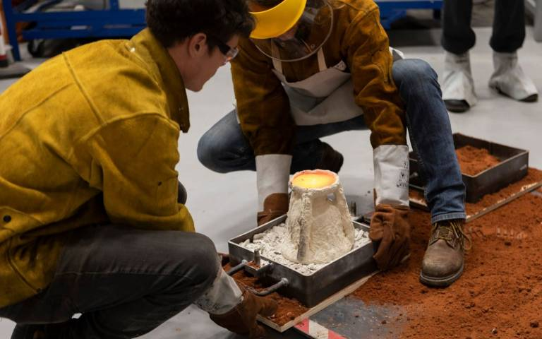 the ceramic shell is pictured just after melted bronze has been poured into it