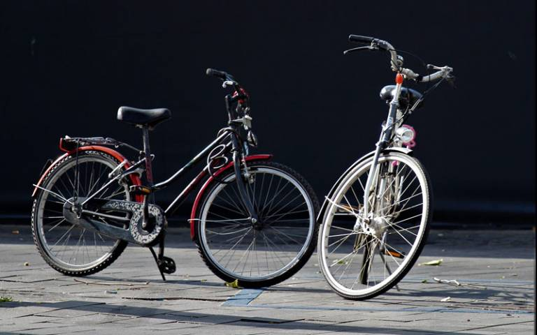Two bicycles standing on a pavement