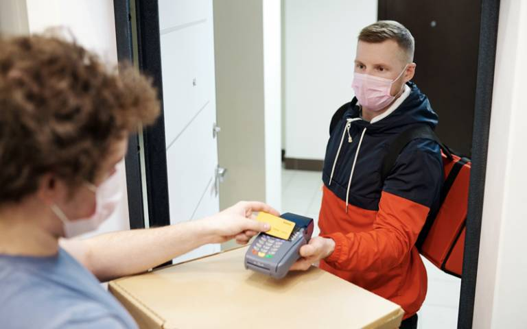 Person wearing a face mask paying for delivery