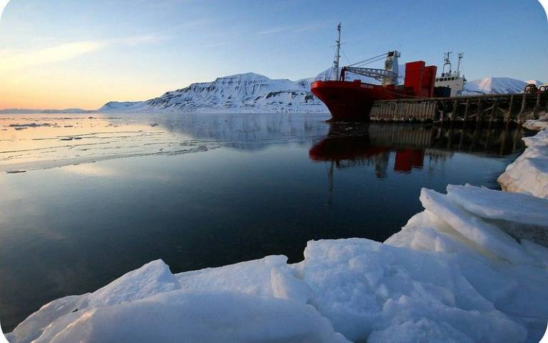 Ship going through water surrounded by ice