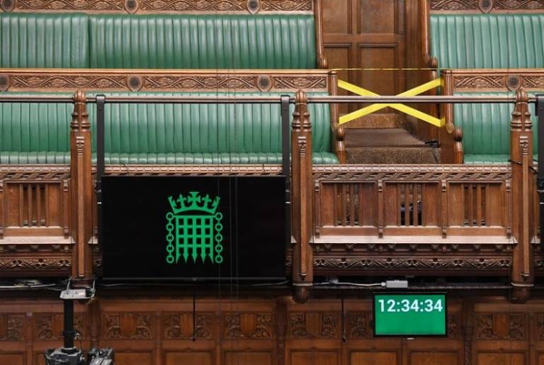 Empty House of Commons with a digital screen and seats cordoned off