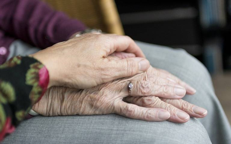 a younger pair of hands on top of a more elderly pair of hands