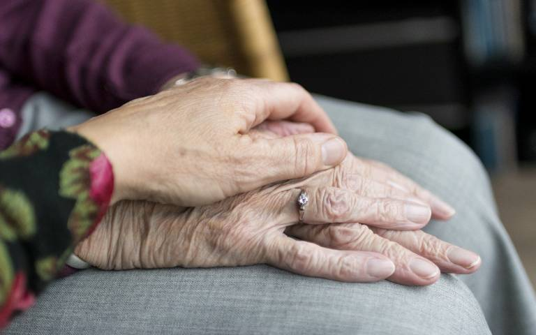 Elderly people holding hands