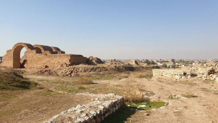 Wide shot of ruins on the outskirts of an Iraqi town in the distance