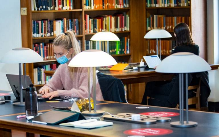 Students studying in the UCL library, socially distant and wearing face coverings