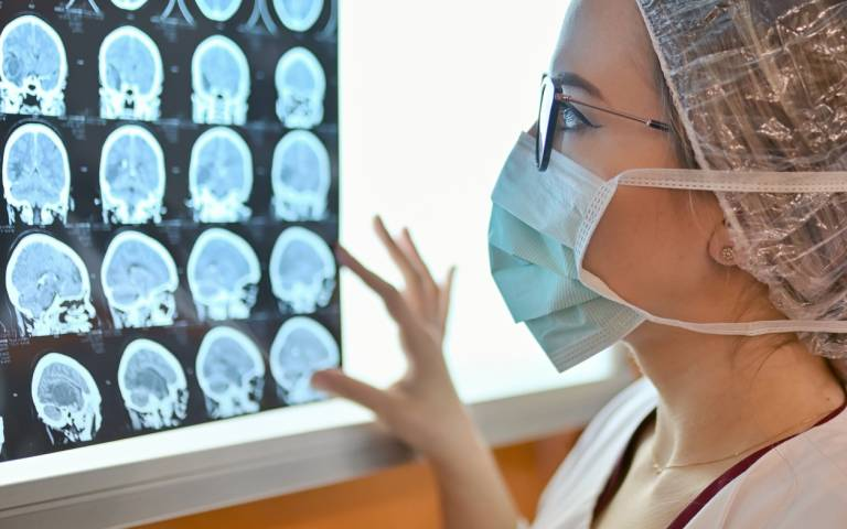 a person in surgical clothing looks at an MRI scan