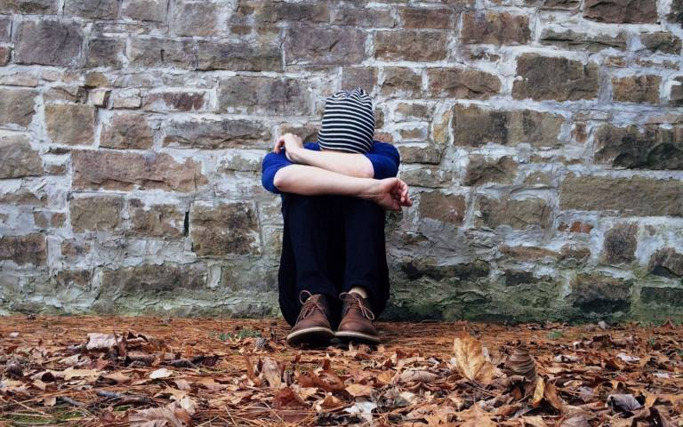 boy leaning against wall with knees hiding face