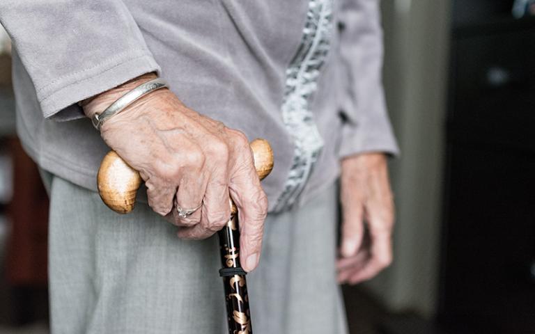 an image of an elderly women holding a walking stick.