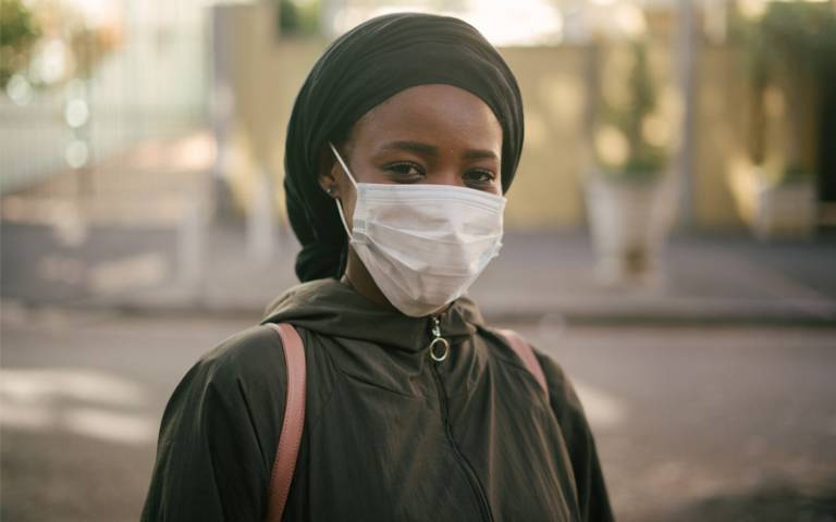 'African-American woman in facemask on city street'