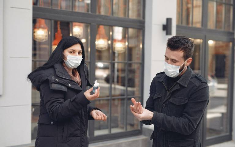 young couple in face masks using hand gel