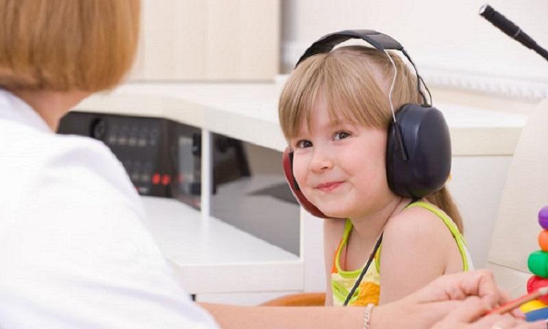 Audiologist testing a little girl