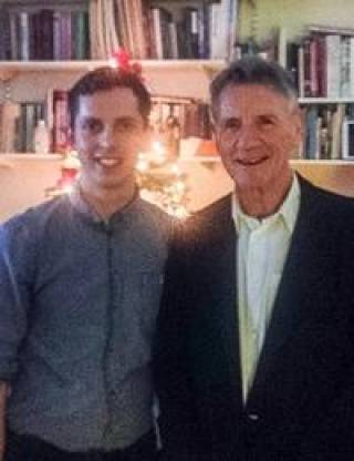 Oli Cheadle being presented with his award by Michael Palin