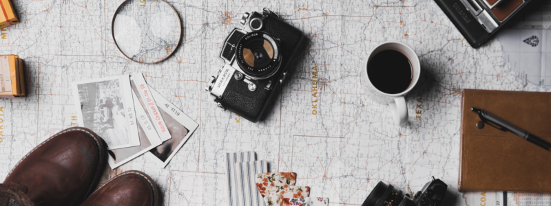Camera, boots, coffee cup, notepad and instant photos.