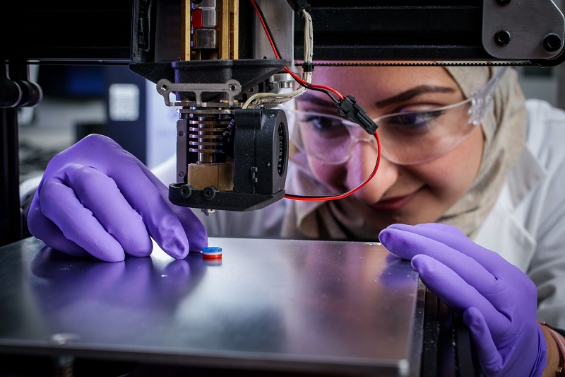 Researcher looking at printed tablet on 3D printer