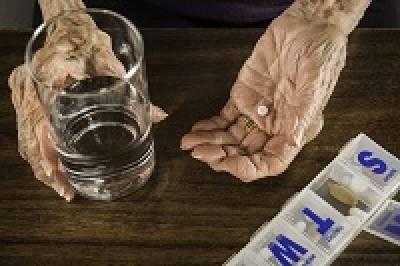 Arthritic hands taking medicines