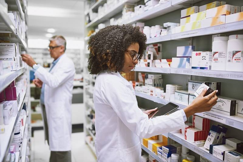 Pharmacists looking at medication on shelves