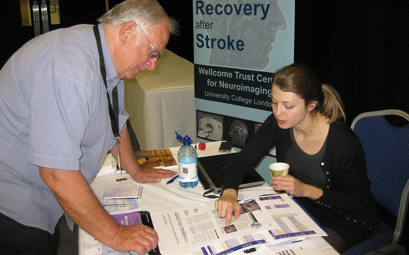 Researcher talking to a stroke survivor at an event