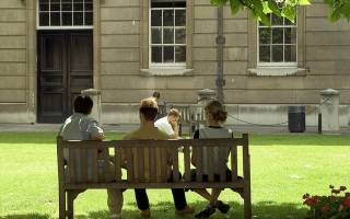 Photo of three people relaxing on a bench in the quad