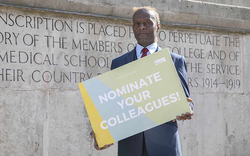 A UCL staff member holding a sign saying