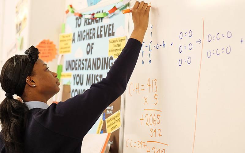 Pupil writing on whiteboard.