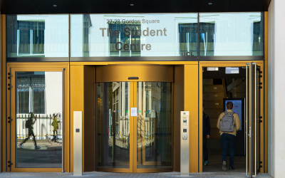 A student walks through the revolving entrance door of the UCL Student Centre.
