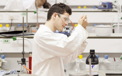Student in white lab coat works with pipet and beaker.