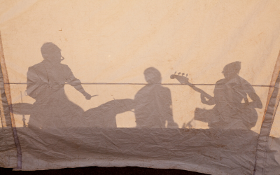Shadow of musicians, drummer, keyboardist, bass guitarist, against a canvas backdrop.