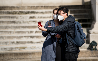 Two students in facemasks take a selfie in the main UCL quad.