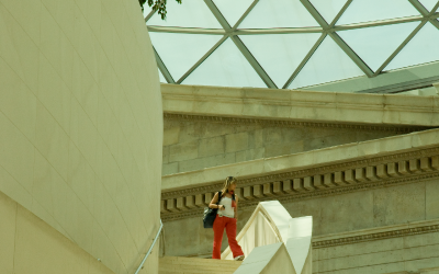 Visitor stands on stairs inside British Museum.