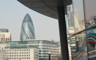 View of the City of London partially reflected in a window.