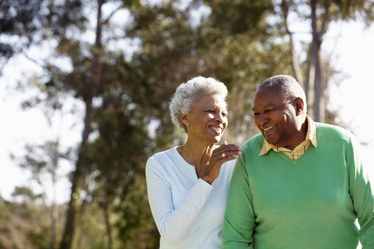 An older couple walking hand in hand smiling